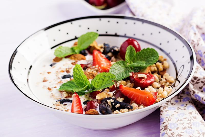 Healthy breakfast - granola, strawberries, cherry, honeysuckle berry, nuts and yogurt in a bowl. Vegetarian concept food stock photography