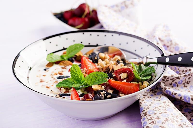 Healthy breakfast - granola, strawberries, cherry, honeysuckle berry, nuts and yogurt in a bowl. Vegetarian concept food stock photos