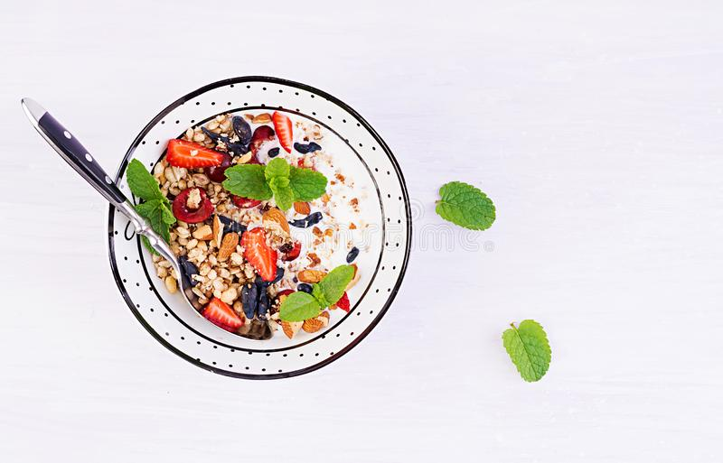 Healthy breakfast - granola, strawberries, cherry, honeysuckle berry, nuts and yogurt in a bowl. Vegetarian concept food. Top view royalty free stock photos