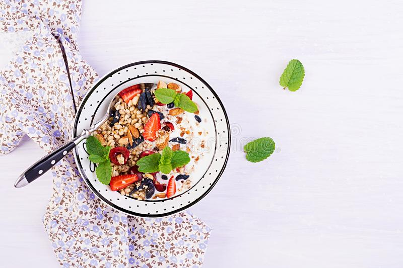 Healthy breakfast - granola, strawberries, cherry, honeysuckle berry, nuts and yogurt in a bowl. Vegetarian concept food. Top view royalty free stock image