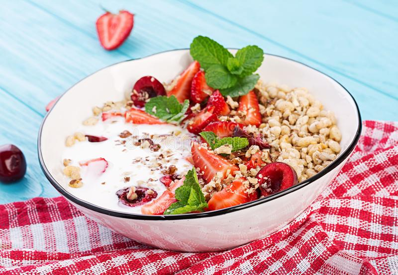 Healthy breakfast - granola, strawberries, cherry, nuts and yogurt in a bowl on a wooden table. Vegetarian concept food stock photos