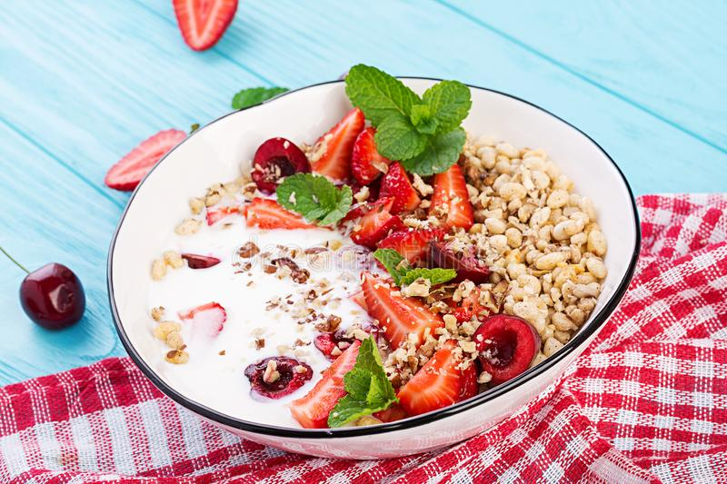 Healthy breakfast - granola, strawberries, cherry, nuts and yogurt in a bowl on a wooden table. Vegetarian concept food stock photography