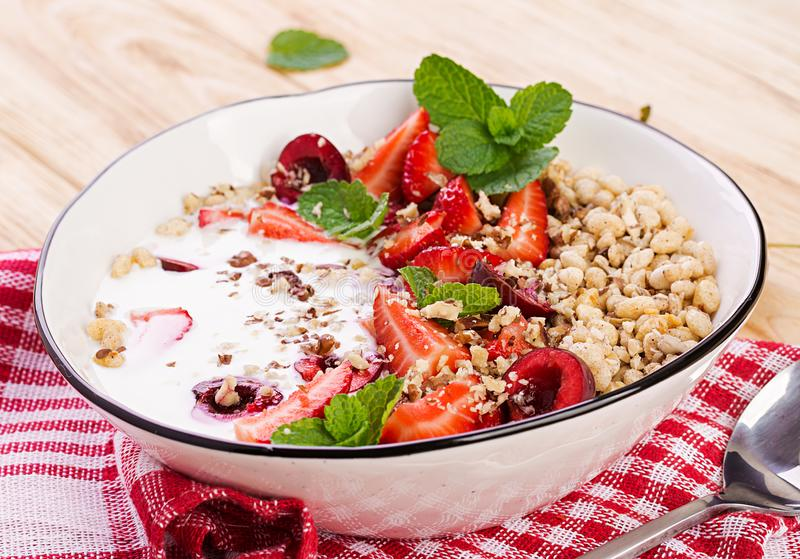 Healthy breakfast - granola, strawberries, cherry, nuts and yogurt in a bowl on a wooden table. Vegetarian concept food royalty free stock photo