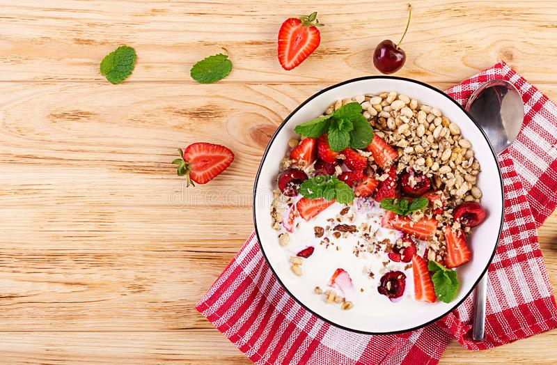 Healthy breakfast - granola, strawberries, cherry, nuts and yogurt in a bowl on a wooden table. Vegetarian concept food. Top view stock photos