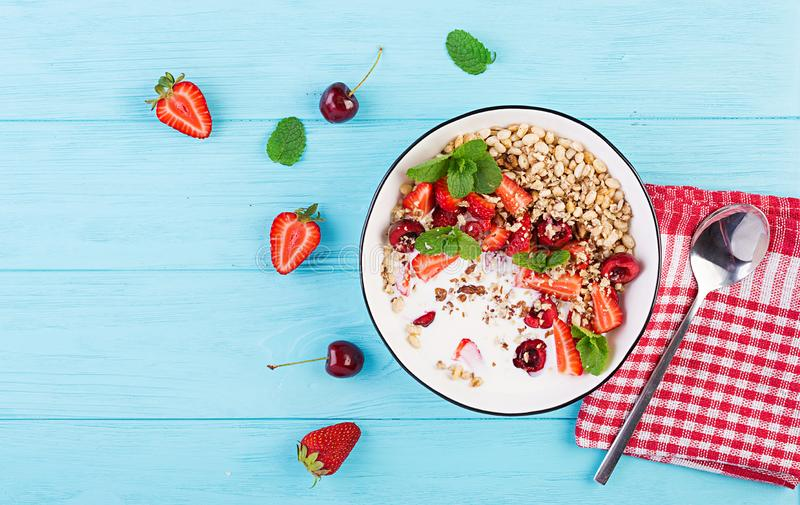 Healthy breakfast - granola, strawberries, cherry, nuts and yogurt in a bowl on a wooden table. Vegetarian concept food. Top view royalty free stock photography