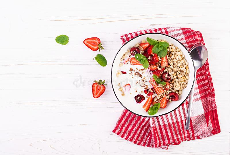 Healthy breakfast - granola, strawberries, cherry, nuts and yogurt in a bowl on a wooden table. Vegetarian concept food. Top view royalty free stock image