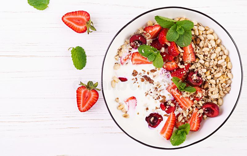 Healthy breakfast - granola, strawberries, cherry, nuts and yogurt in a bowl on a wooden table. Vegetarian concept food. Top view royalty free stock photo