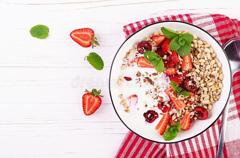 Healthy breakfast - granola, strawberries, cherry, nuts and yogurt in a bowl on a wooden table. Vegetarian concept food. Top view stock image