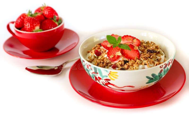 Healthy breakfast granola, strawberry and yogurt on white background. Healthy breakfast of berry granola, strawberries and greek yogurt on white background royalty free stock photos