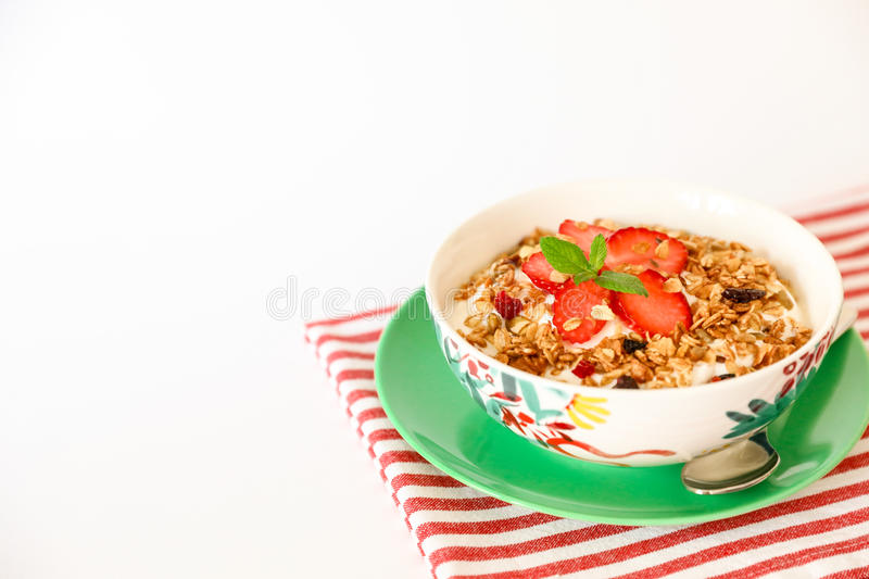 Healthy breakfast granola, strawberry and yogurt on white background. Healthy breakfast of berry granola, strawberries and greek yogurt in a plate on a striped royalty free stock images