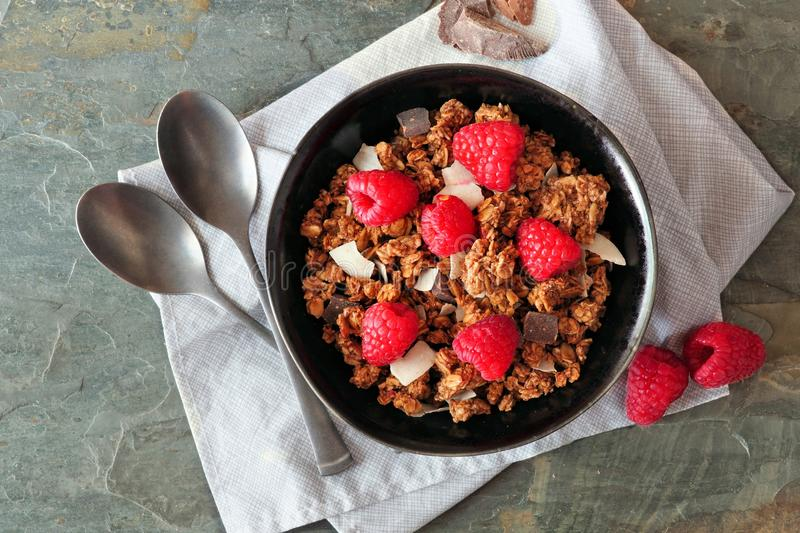 Healthy breakfast granola with dark chocolate, raspberries and coconut. Top view, close up. royalty free stock image