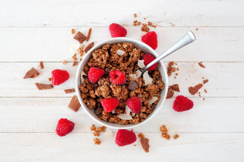 Healthy breakfast granola with dark chocolate, raspberries and coconut. Top view over white wood. Healthy breakfast granola topped with dark chocolate royalty free stock image