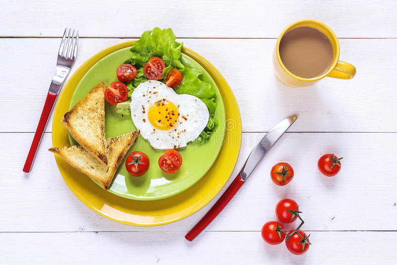 Healthy Breakfast with heart-shaped fried egg, toast, cherry tom. Ato, lettuce on colored plates and coffee. Top view royalty free stock images