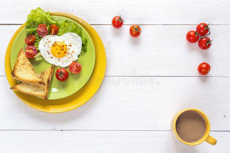 Healthy Breakfast with heart-shaped fried egg, toast, cherry tom. Ato, lettuce on colored plates and coffee. Top view. Place for text stock photos