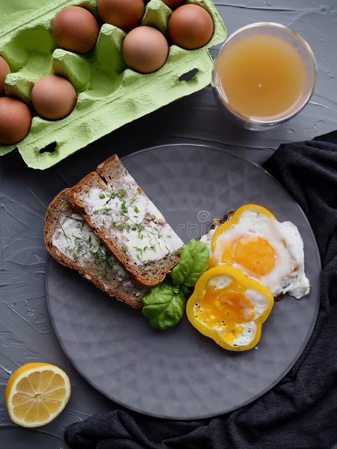 Healthy breakfast with home made bread and eggs and orange juice on grey plate and grey background ideal for culinary blogger or c stock images