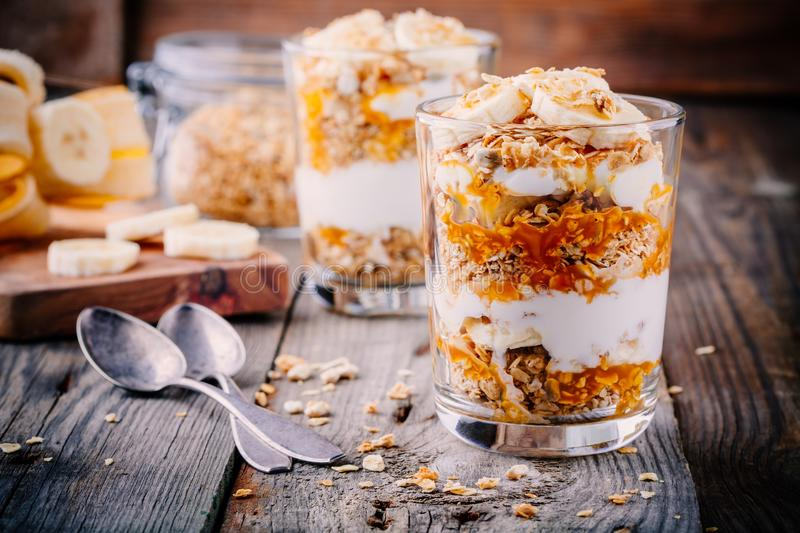 Healthy breakfast. homemade granola with natural yoghurt, banana and caramel sauce. On wooden background stock photo