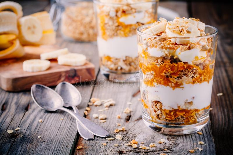 Healthy breakfast. homemade granola with natural yoghurt, banana and caramel sauce. Healthy breakfast. homemade granola with natural yogurt, banana and caramel royalty free stock image