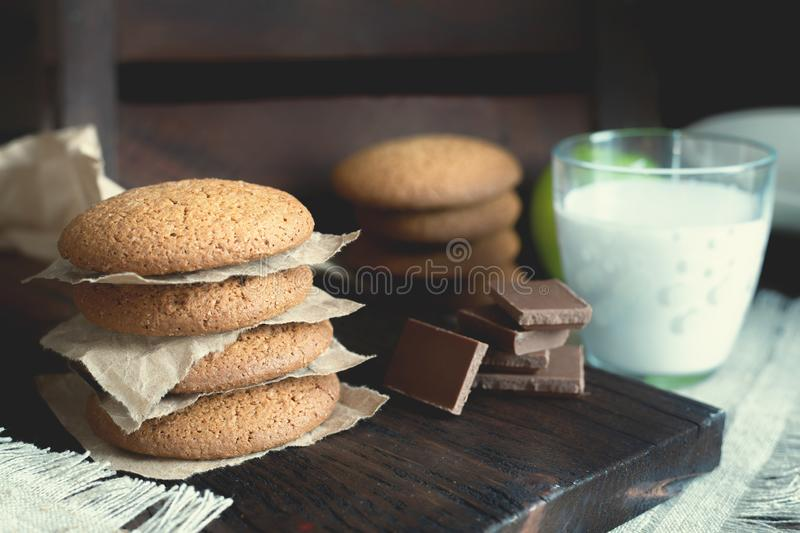 Daily healthy breakfast. Homemade oatmeal cookies, milk, fruit on dark background royalty free stock photos