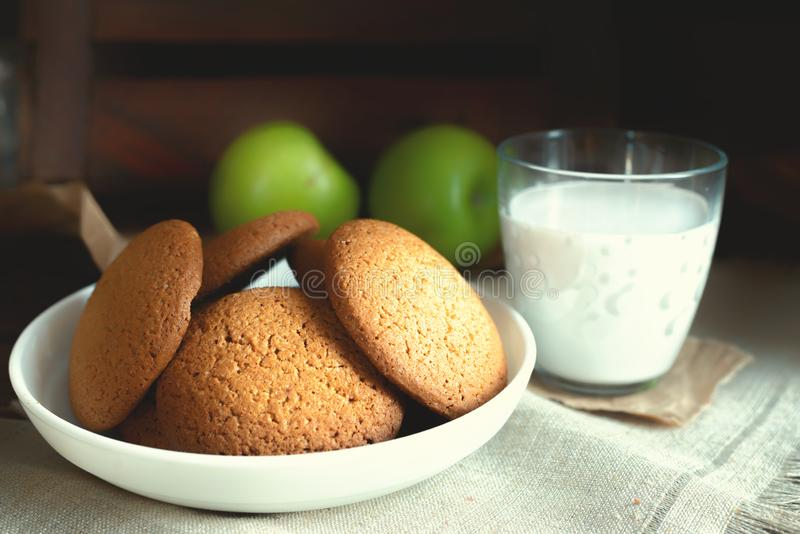 Daily healthy breakfast. Homemade oatmeal cookies, milk, fruit on dark background stock photo