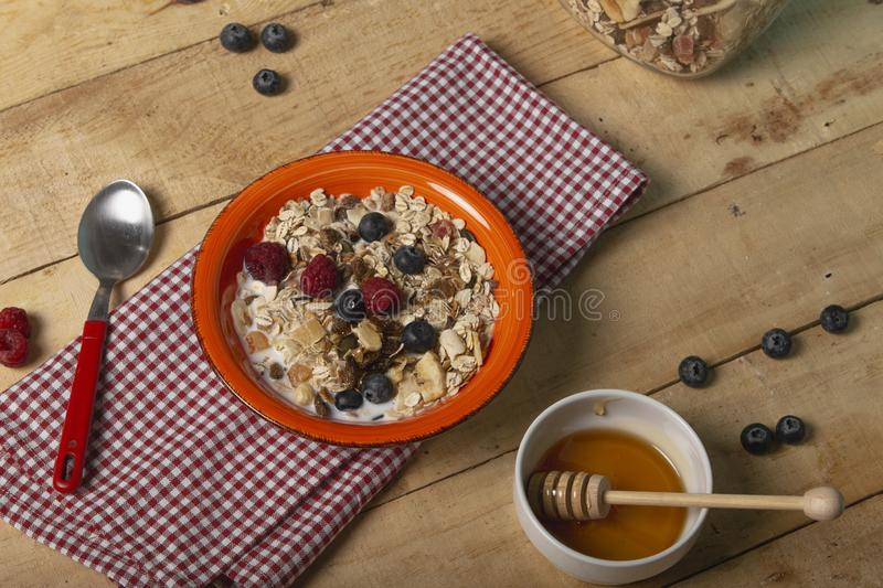 Healthy breakfast honey Oat flakes, fresh berries with raspberry and blueberries on wooden background. Top view.  stock photos
