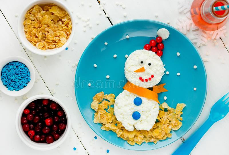 Healthy breakfast idea for kids - christmas snowman from cottage cheese and corn flakes. Food art on plate royalty free stock photos