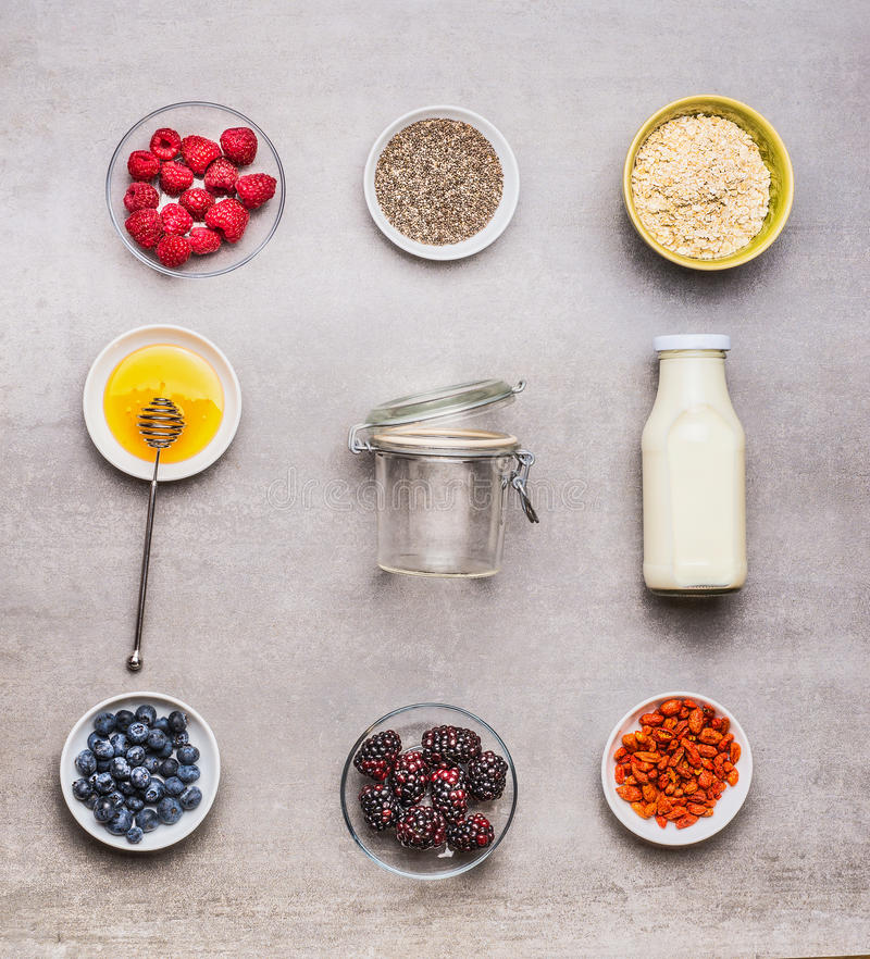 Healthy breakfast ingredients : honey, oatmeal , Chia seeds, Goji berries, fresh berries and bottle of milk with empty glass on stock photography
