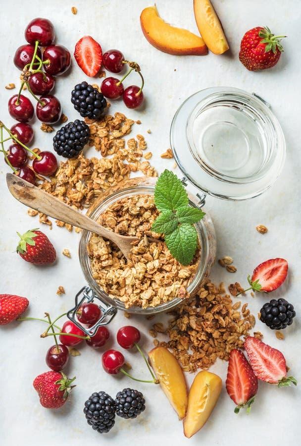 Healthy breakfast ingredients. Oat granola in glass jar with peach, strawberry, sweet cherries, blackberries on light royalty free stock image