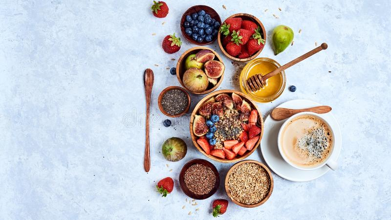 Healthy breakfast and breakfast ingredients, oatmeal with fruits and berries, figs, blueberries, strawberries, flax and chia seeds stock images