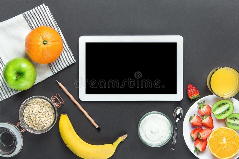 Healthy Breakfast Ingredients Oats Green Apple Banana Strawberries Kiwi Oranges Yogurt Juice on Black Table Top. Mockup Tablet stock image