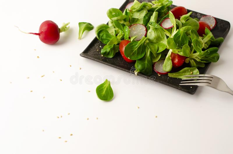 Healthy breakfast or lunch. Fresh vegetable salad of radish, tomatoes and corn salad or Valerianella locusta. Close up on black plate. Diet and vegetarian royalty free stock images