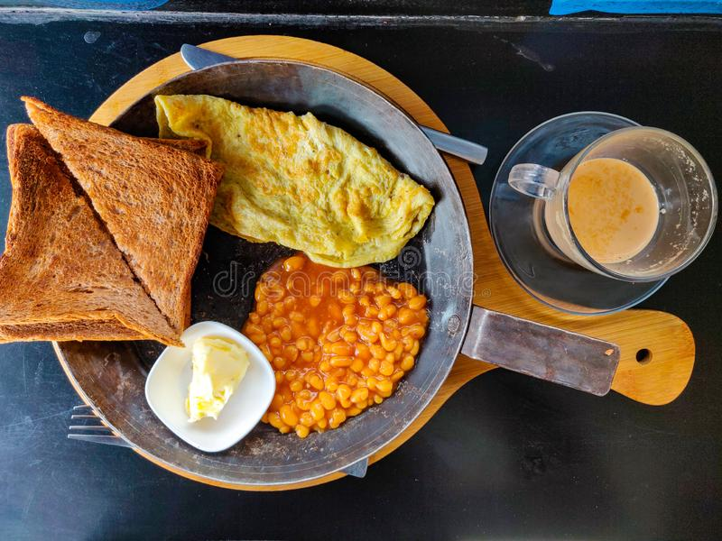 Healthy breakfast. Morning breakfast. Toast, omelette, beans, butter and tea served in a pan. Top view stock photography