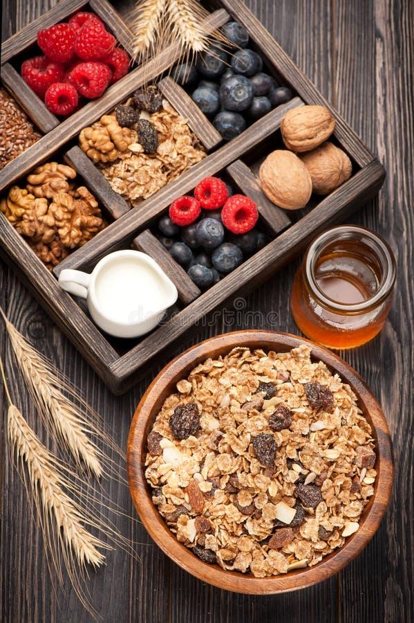Healthy breakfast with muesli, granola. Honey, nuts, blueberries, raspberries, milk. Box with food for healthy breakfast stock photos