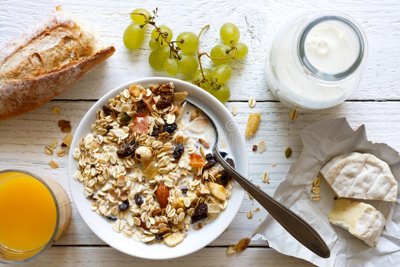 Healthy breakfast with muesli, grapes, cheese and juice on rustic white table from above. stock photo