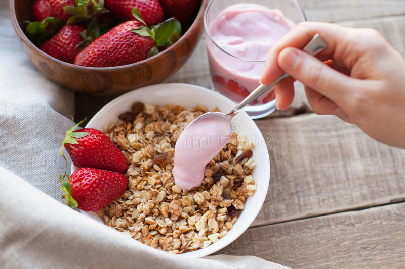 Healthy breakfast. Muesli and yogurt with strawberries. A woman`s hand puts a spoonful of yogurt in the muesli royalty free stock images