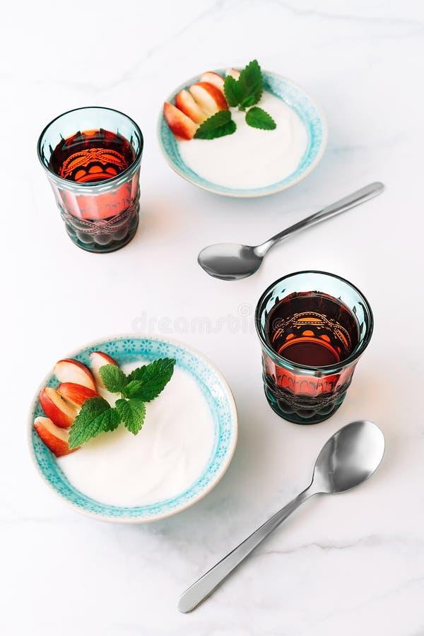 Healthy breakfast of natural greek yoghurt, fruit and juice on marble table royalty free stock image