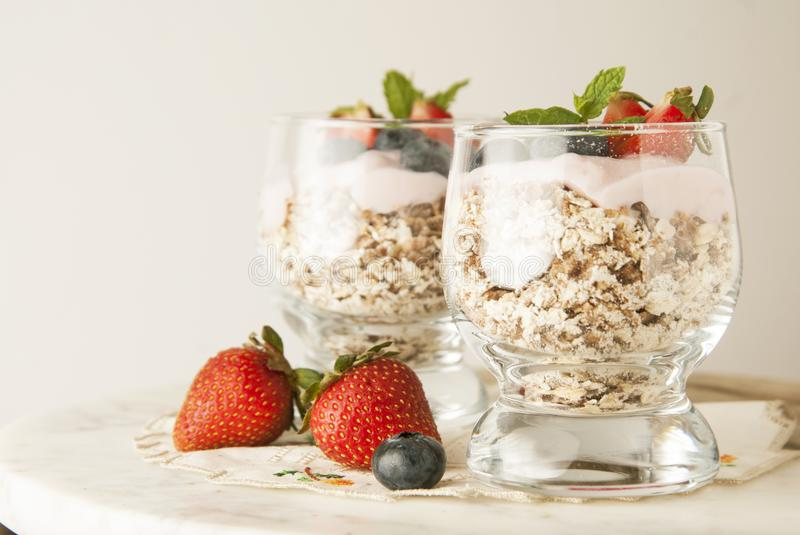 Healthy breakfast, oat meal with fruits: bluebery, strawbery and min, parfait in a glass on a rustic background. Healthy food. royalty free stock image