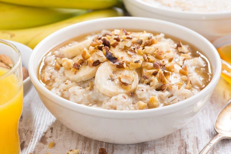 healthy breakfast - oatmeal with banana, honey and walnuts royalty free stock photography