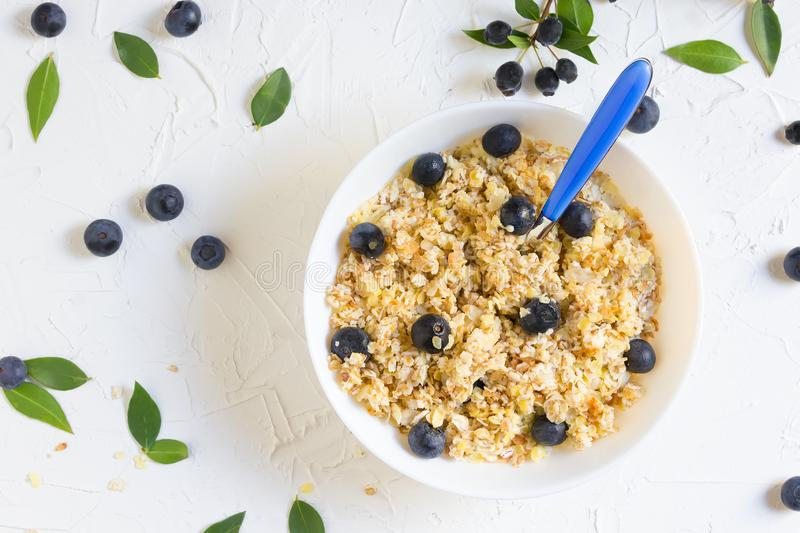 Healthy breakfast. Oatmeal with blueberries, a teaspoon, top angle, top view, flatlay stock photography