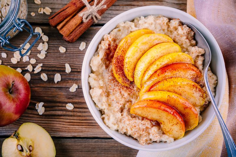 Healthy breakfast: oatmeal bowl with caramelized peaches, cinnamon and honey royalty free stock images