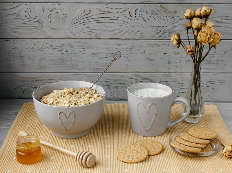 Healthy wholegrain breakfast: oatmeal, milk, biscuits, honey and vase with roses. Healthy breakfast: oatmeal cereal, cup of milk, jar of homemade jam, oatmeal royalty free stock photography