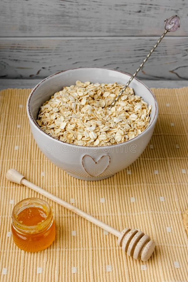 Healthy wholegrain breakfast: oatmeal, milk, biscuits, honey and vase with roses. Healthy breakfast: oatmeal cereal, cup of milk, jar of homemade jam, oatmeal stock images
