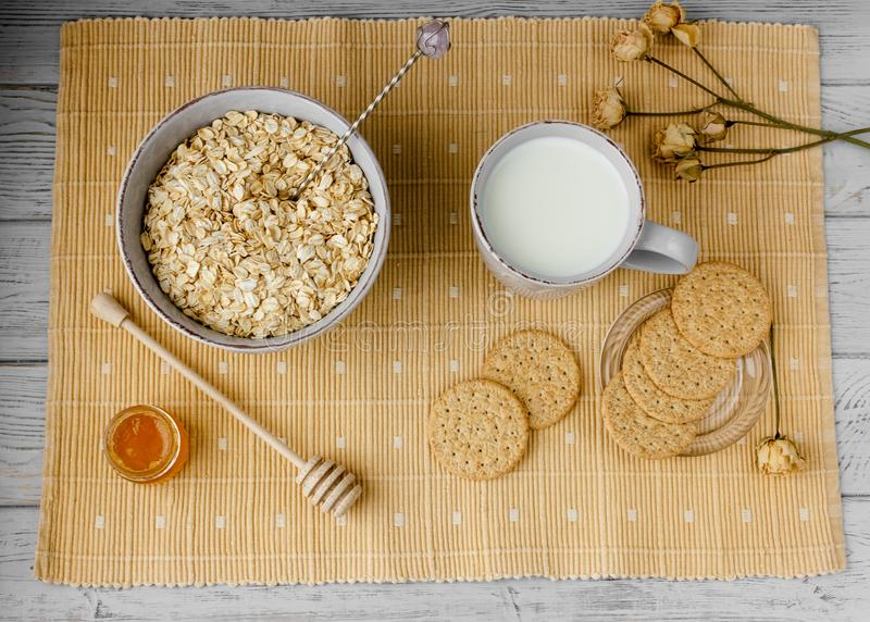 Healthy wholegrain breakfast: oatmeal, milk, biscuits, honey and vase with roses. Healthy breakfast: oatmeal cereal, cup of milk, jar of homemade jam, oatmeal royalty free stock photo