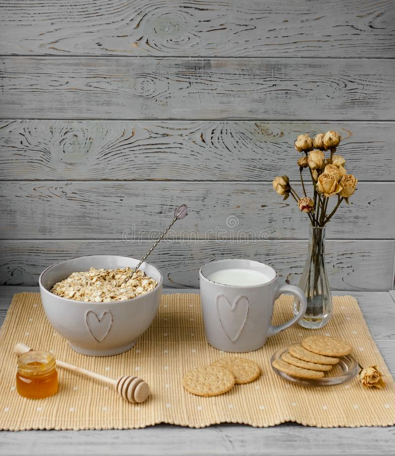 Healthy wholegrain breakfast: oatmeal, milk, biscuits, honey and vase with roses. Healthy breakfast: oatmeal cereal, cup of milk, jar of homemade jam, oatmeal stock image