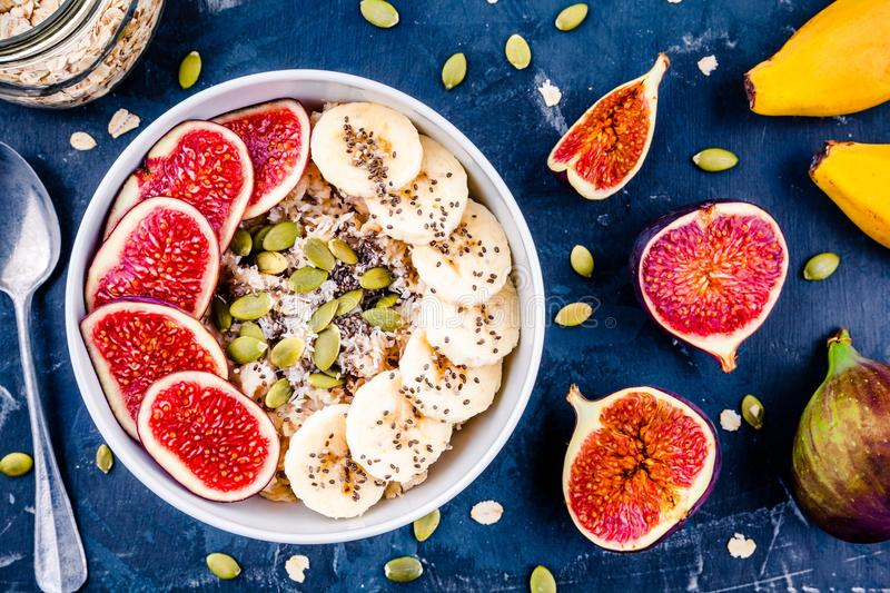 Healthy breakfast: oatmeal with fresh figs, bananas, pumpkin seeds, coconut and chia seeds royalty free stock images
