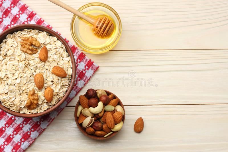 Healthy breakfast. oatmeal, honey and nuts on white wooden table. Top view with copy space royalty free stock photo
