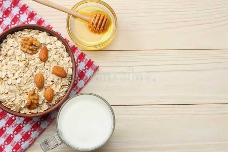 Healthy breakfast. oatmeal, honey and nuts on white wooden table. Top view with copy space stock photos