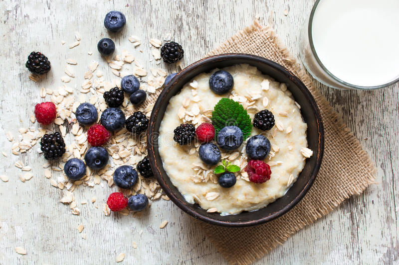 Healthy breakfast. oatmeal porridge in a bowl with glass of milk royalty free stock photography