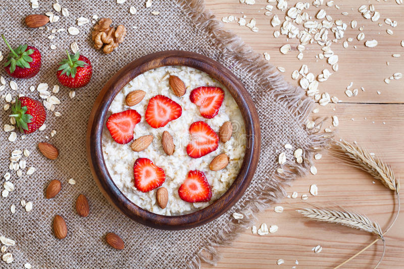 Healthy breakfast oatmeal porridge diet nutririon. With strawberry and nuts. Organic vegetarian meal. Vintage wooden table background. Rustic style and natural stock photography