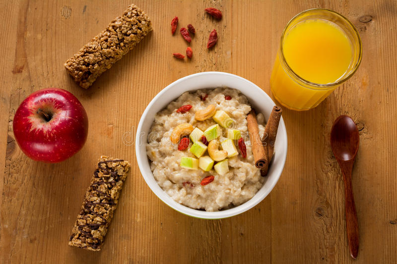 Healthy breakfast, oatmeal porridge with fruits, nuts and juice royalty free stock image