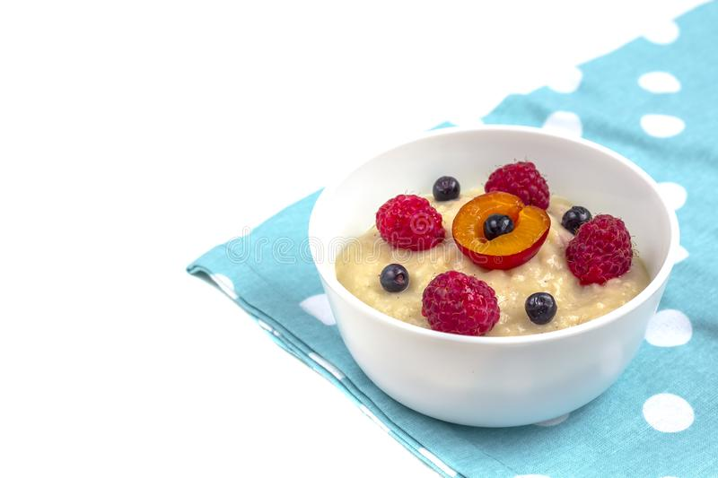 Healthy breakfast porridge for kids. Bowl of baby food on a fabric isolated on white. T. He concept of proper nutrition and healthy food. Copy space royalty free stock photography